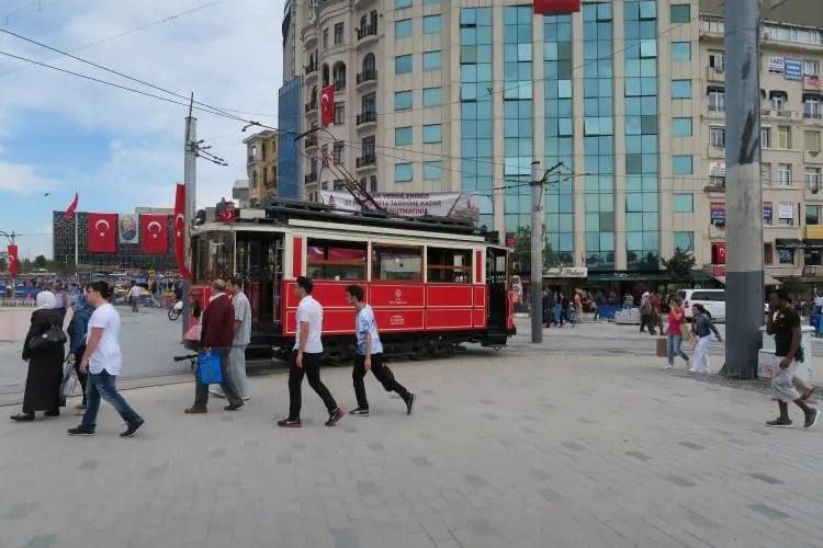 Eine rote Straßenbahn fährt in die Istiklal Caddesi, vom Taksim Platz. Vorbei an Läden die Hamburger verkaufen.