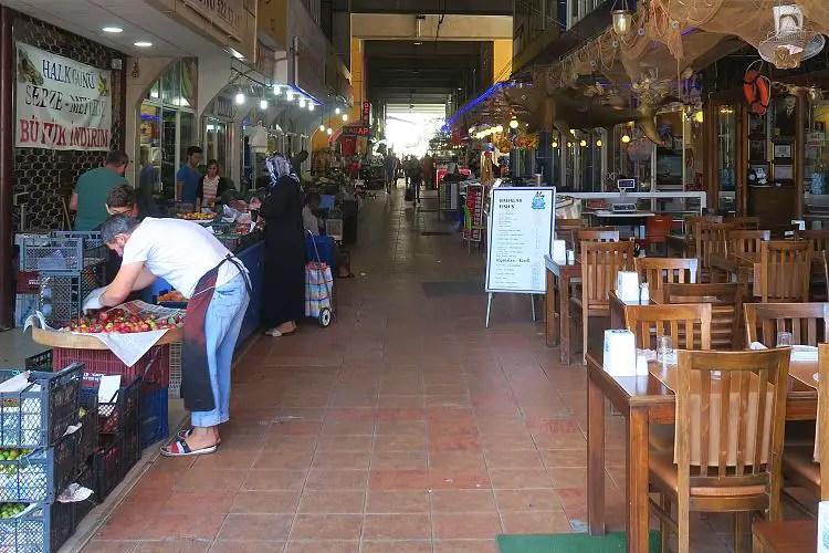 Das Innere der Fisch- und Markthalle mit Geschäften und Restaurants mit Sitzplätzen. Die Halle ist überdacht.