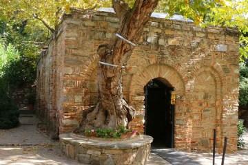 Eingang des Haus der Mutter Maria, es steht in einem kleinen Park und ist von Laubbäumen überwachsen.