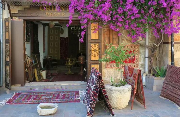 """Eingang eines Teppichhändlers mit Teppichen vor der Tür und der Aufschrift """"Orient Basar"""""""