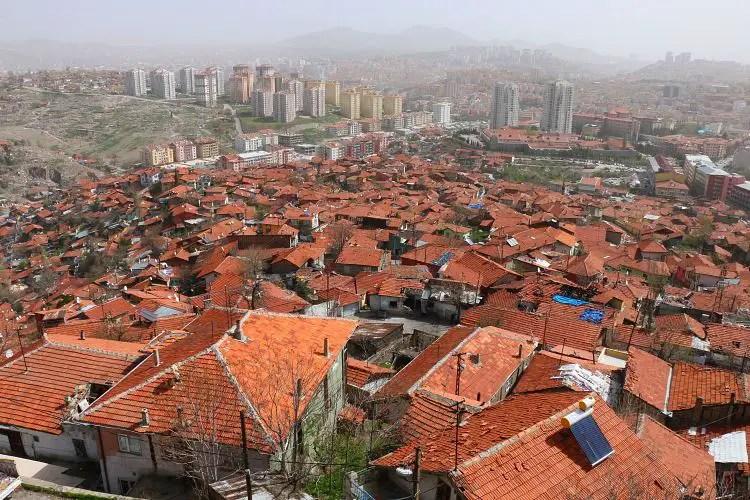 Rotem Dächer der Altstadt mit mehrstöckigen Wohnhäusern im Hintergrund auf Hügeln