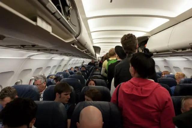 Das Innere einer Flugzeugkabine. Menschen steigen gerade in das Flugzeug ein und verstauen ihr Handgepäck.