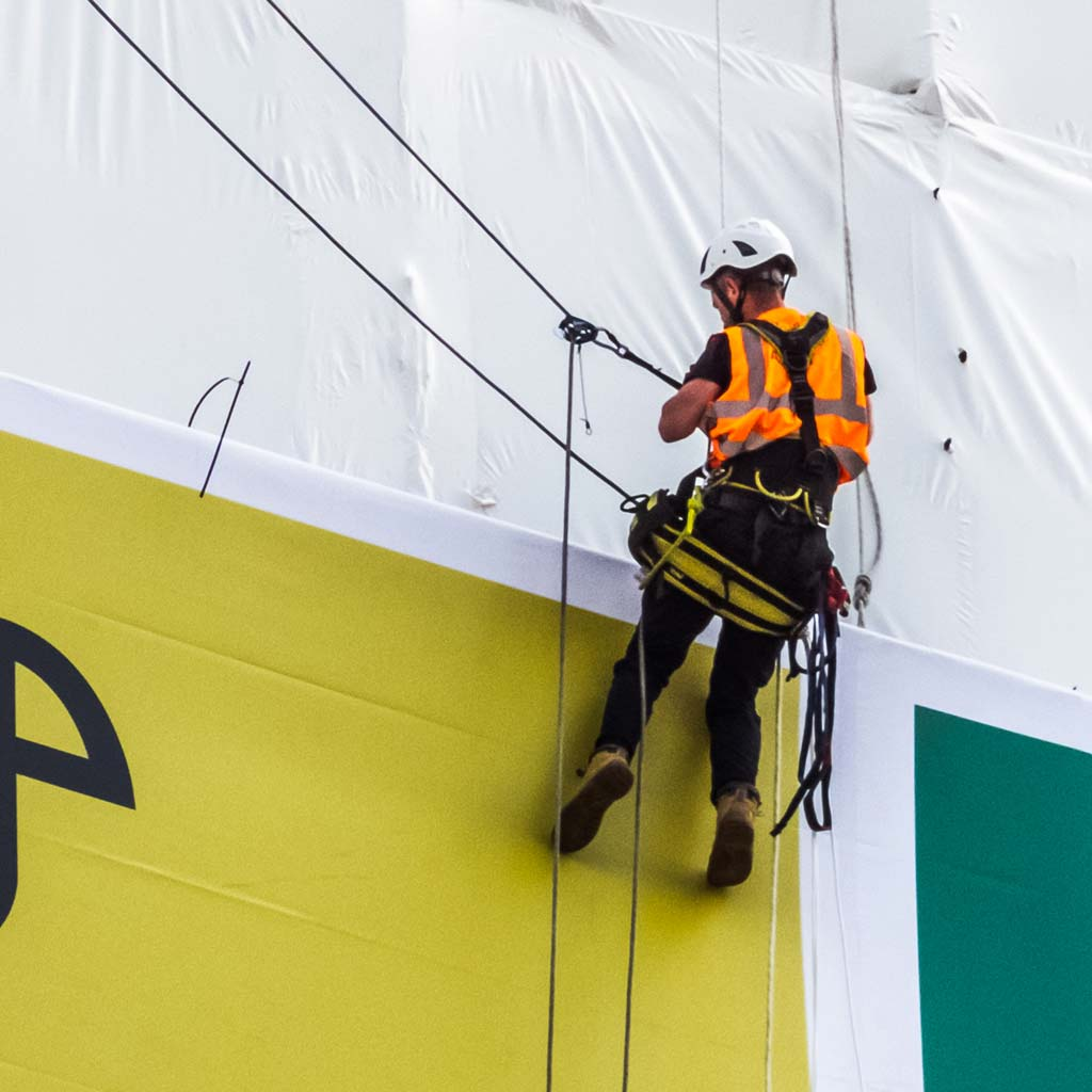 Abseiler Installing Banner on scaffolding around Eagle House Bracknell for Thomas homes