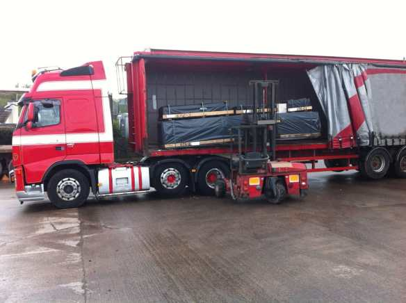 Log cabin deliveries take place with an articulated lorry and a demountable forklift.