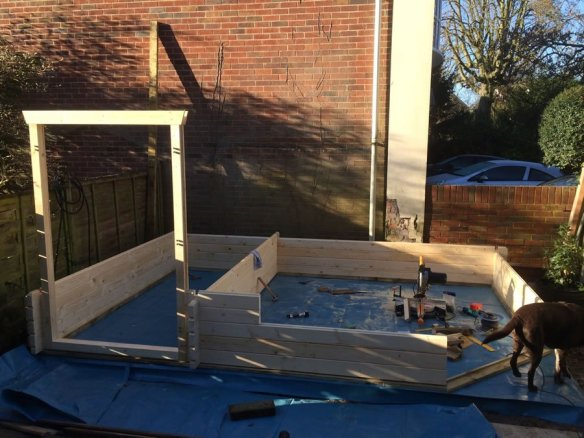 The build progresses with the shed door frame in place.