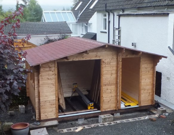 Roof shingles being fitted. It is a good idea to remove the doors by lifting off the hinges