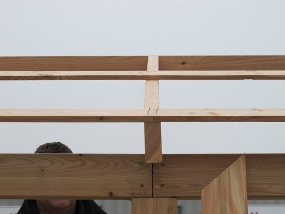 Tacking a roof board, all around on the first layer flush with the bottom of the rafter.
