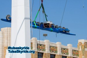Tulsa Skyride tower 5 maintenance: The north battery is lowered to the ground. Fairgrounds Pavilion is in the background.