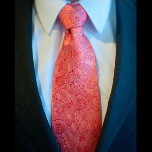 ピンクのペイズリーネクタイと紺スーツ