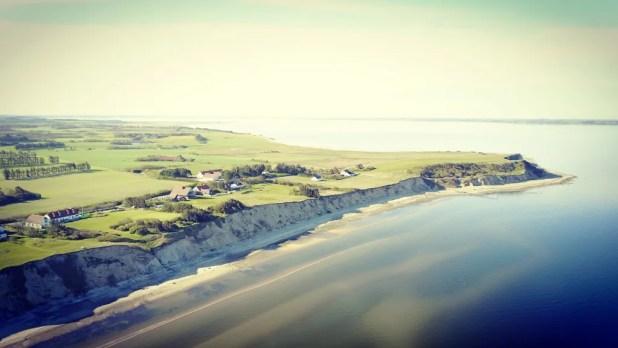 Ertebølle er et besøg værd af flere årsager. Ikke alene er stranden velegnet til badning, men hvis du spadserer lidt ned ad stranden mod syd fra badebroen, møder du en strækning med 20 m høje skrænter med tydelige lag af aflejret moler og aske – de ældste 55 mio. år gamle. Stranden er rig på fossiler og forstenet træ og havdyr og et must for geologi- og arkæologientusiaster. (Foto: Himmerlands Vestkyst)