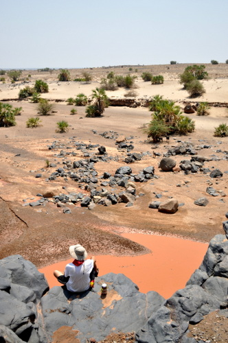 Rob sits on a ridge above the waterhole and takes in the view.