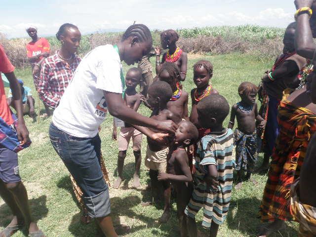 Nurse Beatrice Eyomo giving polio drops to children in Nangolei village