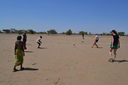Sara and Megan (Team TBI goalie) kick the ball with a group of local boys.