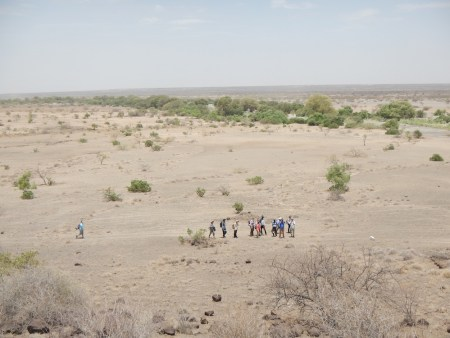 The students crowd around as Dr. Martins discusses the baboons on the nearby outcrop.