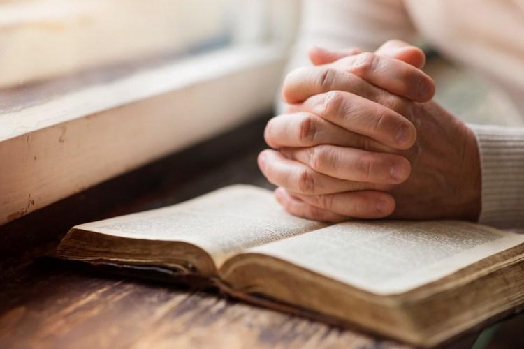 Un libro di preghiere con mani giunte