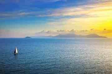Tramonto sull'Isola d'Elba con una barca che veleggia nel mare