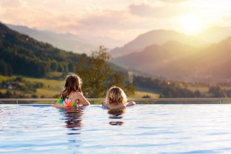 Bambini guardano il panorama da una piscina in Toscana