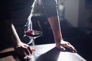 Sommelier con bicchiere di vino rosso in mano con raggio di luce