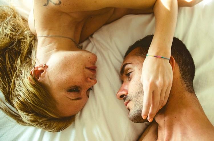 Una giovane coppia eterosessuale su letto con lenzuola bianche