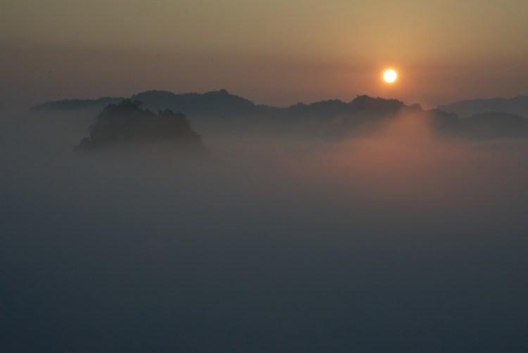 Fitta nebbia sulle montagne con il sole che sorge dal mare