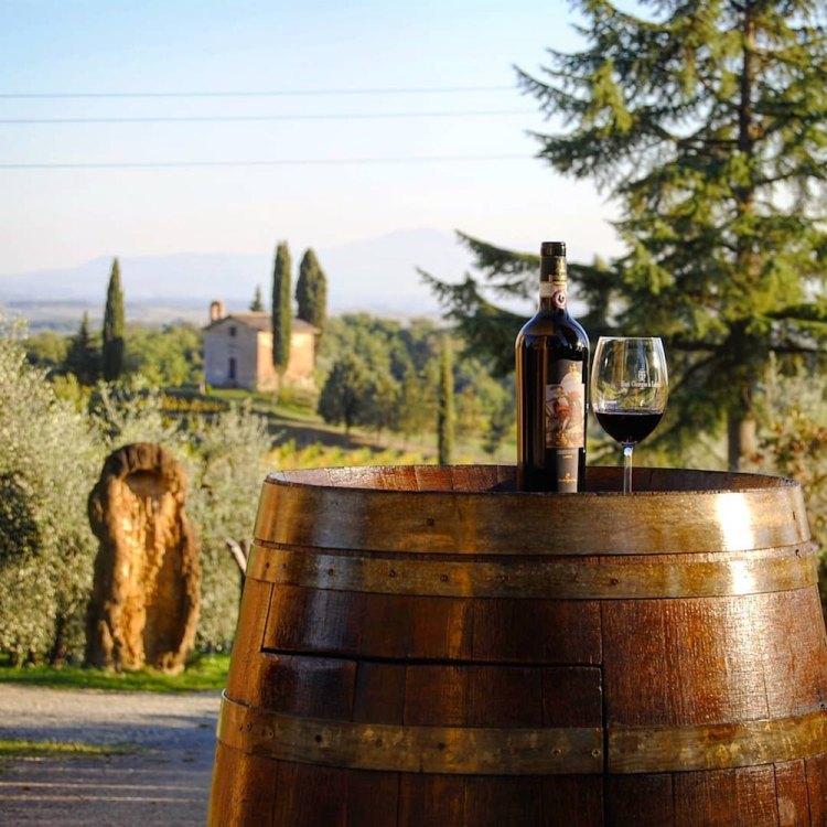 Bottiglia di vino con campagna toscana come sfondo alla chiesetta di San Giorgino, nella tenuta San Giorgio a Lapi