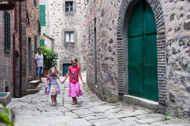 2 little girls walking in village street