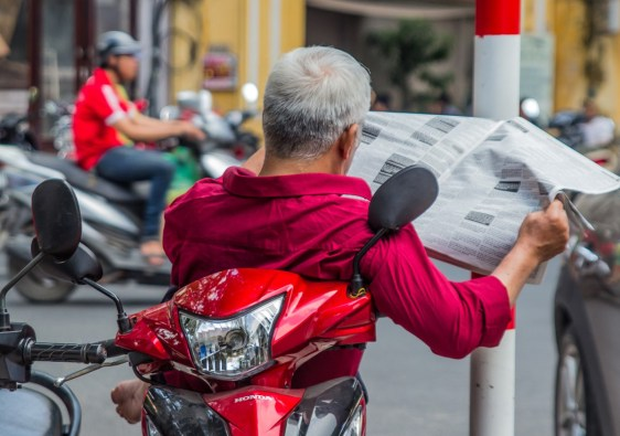 vietnamita legge le notizie di attualità sul motorino