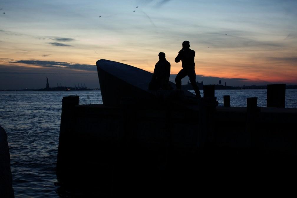 Monumento de battery park a los marineros mercantes con la estatua de la libertad al atardecer