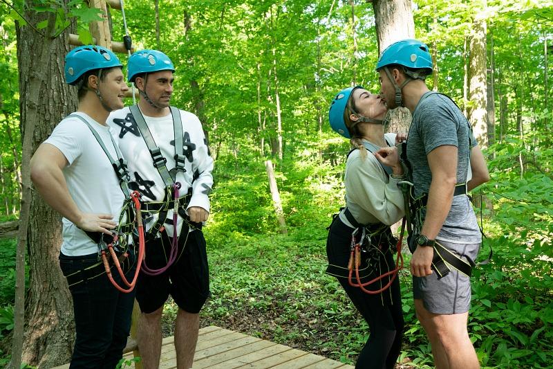 Four people prepare to zipline.