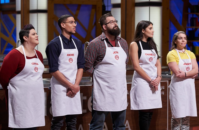 Five people, wearing cooking aprons, stand next to one another.