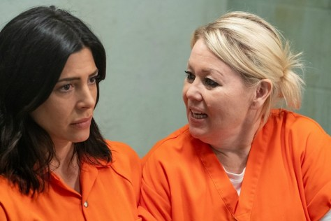 Two women, wearing orange prison jumpsuits, sit in a cell.