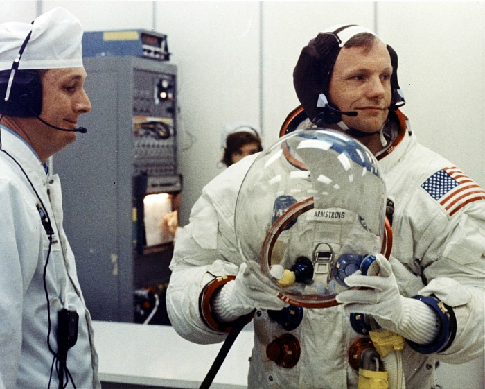 A man stands, wearing an astronaut's suit.