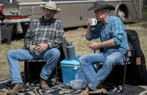 Two men sit in chairs, dressed as cowboys.