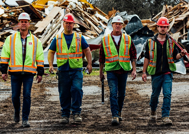 Four men, wearing safety equipment, stand in front of a pile of garbage.