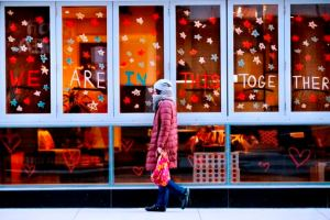 A woman walks by restaurant windows with the words WE ARE IN THIS TOGETHE written outside the Aloft hotel in the Gold Coast neighborhood on April 1, 2020, in Chicago. (Armando L. Sanchez - Chicago Tribune)