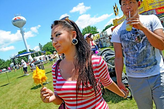 Pang Vang enjoys her mango on a stick as she walks with her friend Paul Xiong at Taste of Minnesota in Waconia Thursday July 3, 2014. The festival was moved to Waconia after flooding at Harriet Island. Vang is from Eau Claire; Xiong is from Minneapolis. (Pioneer Press: Jean Pieri)