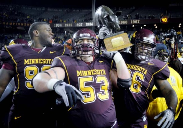 "Minnesota players Sean Ferguson, left, D.J. Burris, center and Brandon Kirksey, right, carry the ""Floyd of Rosedale"" trophy off the field after Minnesota upset No. 24th Iowa 27-24 in an NCAA college football game Saturday, Nov. 27, 2010 in Minneapolis. (AP Photo/Tom Olmscheid)"