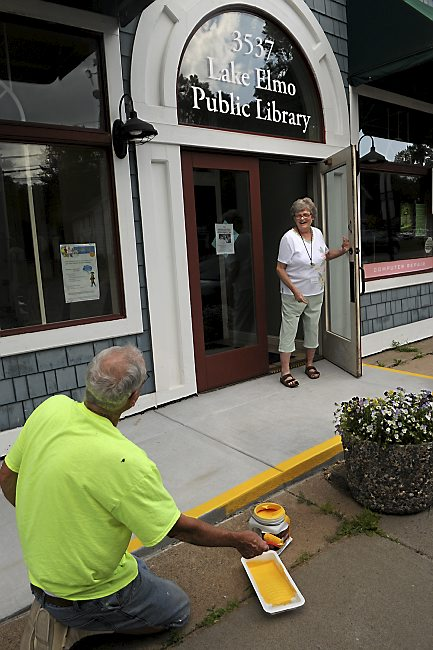 A woman talks to Steve DeLapp, president of the library board, as he paints a safety stripe around the raised concrete pad at the Lake Elmo Library on July 17, 2013. (Jean Pieri / Pioneer Press)