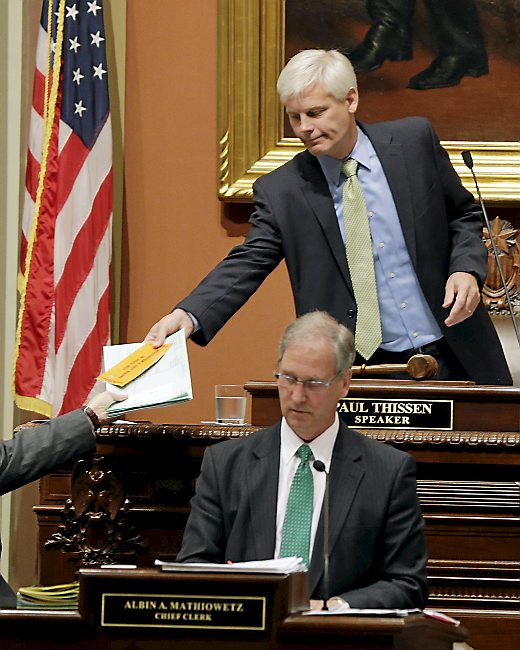 Speaker of the House Paul Thissen hands a copy of the disaster relief bill to an aide as a special session of the Legislature called to fund relief for June storms and floods in Minnesota convened at the Capitol, Monday, Sept. 9, 2013 in St. Paul, Minn. In lower center is Chief Clerk Albin A Mathiowetz. (AP Photo/Jim Mone)