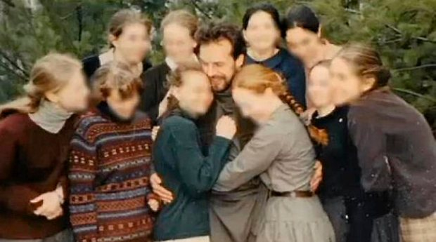 """Victor Barnard, 52, the leader of River Road Fellowship, poses with the 10 """"Maidens"""" he chose to be """"sacrificed to God"""" at Shepherd's Camp in Finlayson, Minnesota, in an undated photo. Their faces have been blurred to protect their identity. (Photo courtesy of KMSP Fox 9 News)"""