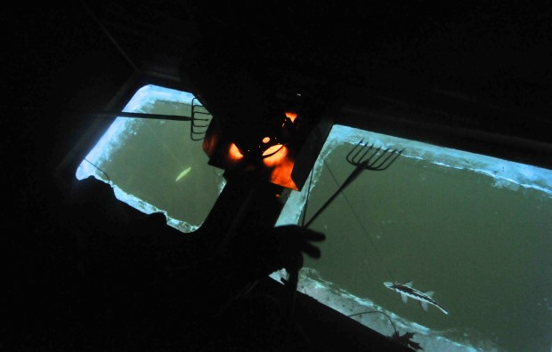 The interior of a two hole darkhouse. The illumination in the holes is provided by daylight shinning through eight inches of ice on Crosslake, north of Brainerd, Friday morning, January 13, 2011. Between the holes rest a propane powered heater. (Pioneer Press: John Autey)
