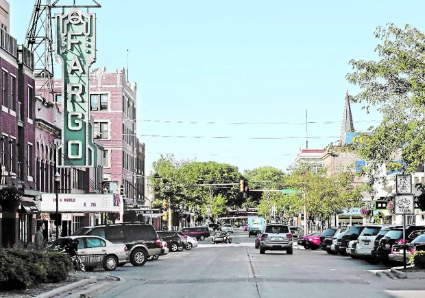 This photo taken on Sept. 16, 2013, cars move through downtown Fargo, N.D., with the picturesque Fargo Theatre, left. (AP Photo/The Forum, Michael Vosburg)