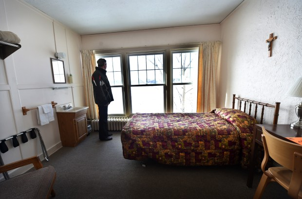 Father Patrick McCorkell, retreat director at the Demontreville Jesuit Retreat House in Lake Elmo, shows a typical room, which includes a bed, sink, desk and chair. (Pioneer Press: Jean Pieri)