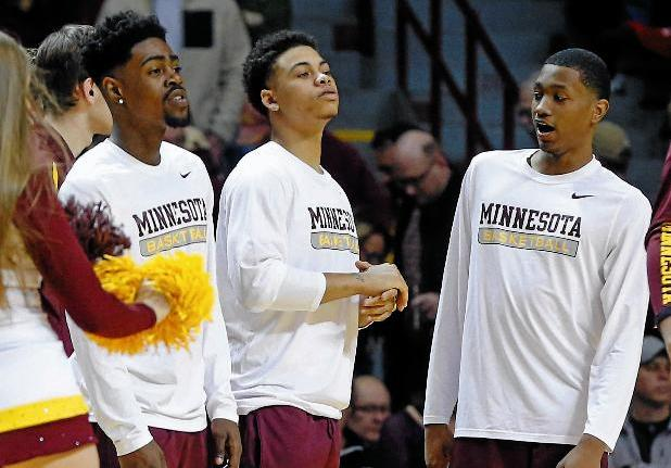 Minnesota's Kevin Dorsey, Jr., left, Nate Mason, center, and Dupree McBrayer, right, stand aside during warmups before the game Wednesday at home, after being suspended for the rest of the season for undisclosed team violations. (AP Photo/Jim Mone)
