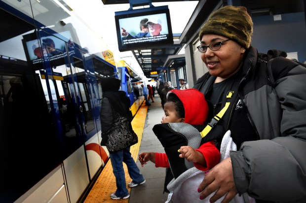 LaShay Thomas of St. Paul, and her great niece Nyanna Johnson, 10 months, prepare to board the Green Line on University and Snelling on Wednesday, March 9, 2016. The Snelling Green Line light rail transit stop is close to the United FC soccer stadium and might get a branding makeover. (LaShay has a day off from her job at Sears and so went shopping with her great niece.) (Pioneer Press: Jean Pieri)