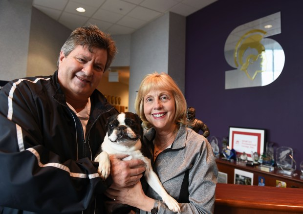 Mark and Cori Hohenwald, owners of Spartan Promotional Group in Oakdale, with the company mascot Scooter, a Boston Terrier. March 16, 2016. (Pioneer Press: Scott Takushi)