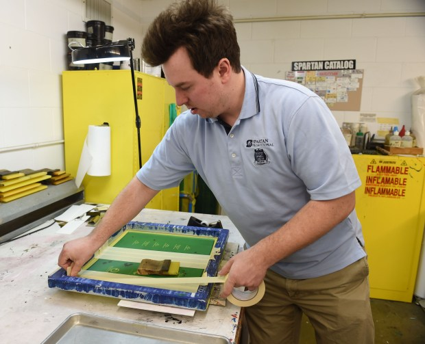 Signmaker Matt Scott preps a screen before silkscreening an order of Girl Scout name badges at Spartan Promotional Group in Oakdale, March 16, 2016. (Pioneer Press: Scott Takushi)