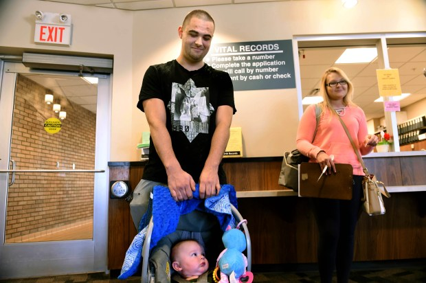 Jesse Hunt holds son Kurt Hunt, 4-months old, as fiancee Taylor Russell and Hunt apply for a marriage license at the Ramsey County Public Health Center in St. Paul on Wednesday, April 13, 2016. Minnesota law currently requires a five-day waiting period to get a marriage license. (Pioneer Press: Scott Takushi)