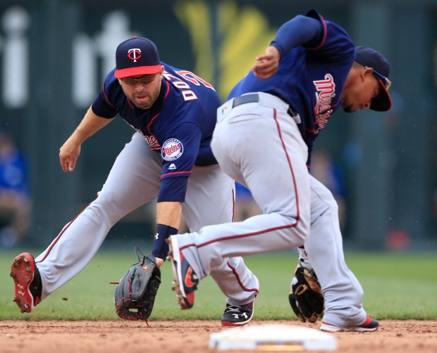 Minnesota Twins shortstop Eduardo Escobar, right, fields a ball hit by Kansas City Royals' Alex Gordon in front of second baseman Brian Dozier (2) during the seventh inning. Gordon was out at first base on the play. (AP Photo/Orlin Wagner)