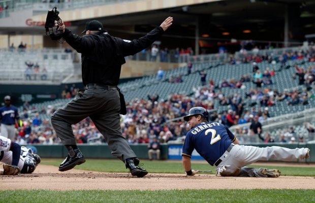 Milwaukee Brewers' Scooter Gennett looks back as plate umpire Tim Timmons makes the safe call as Gennett beat the tag by Minnesota Twins catcher John Ryan Murphy to score from third on a sacrifice fly by Chris Carter in the first inning of a baseball game Tuesday, April 19, 2016, in Minneapolis. (AP Photo/Jim Mone)